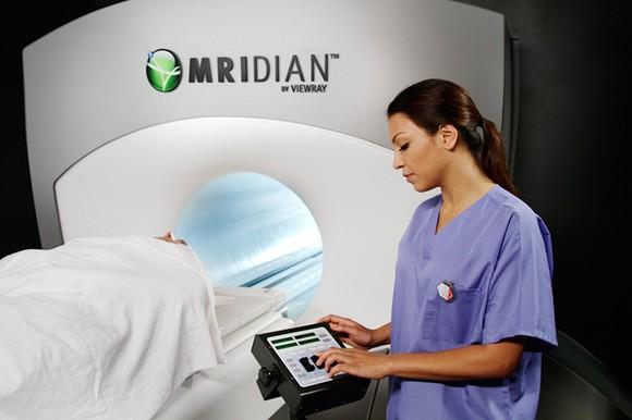 A nurse stands beside a MRIdian system.