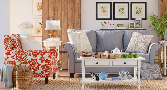 A Wayfair-advertised living room including a chair, couch, coffee table, lamp, and pictures on the wall.