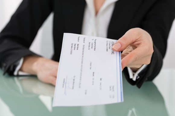 A professional woman handing over a paycheck.