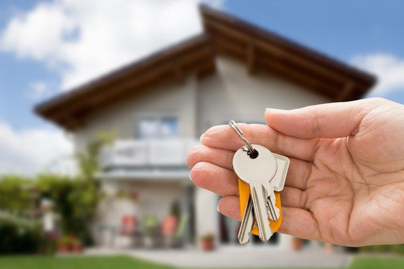 Hand holding house keys with a home in the background