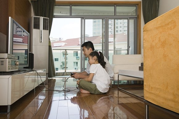 Father and daughter in a living room playing a video game together.