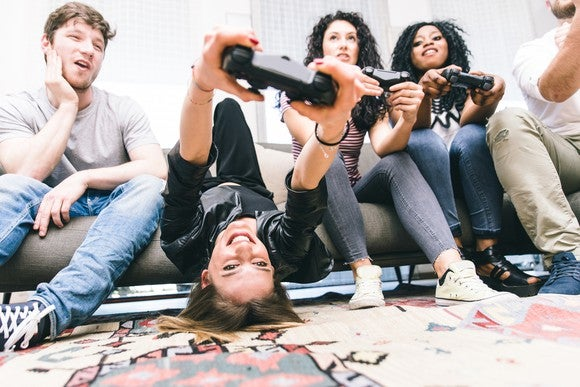 A group of young people sitting on a couch enjoying playing video games together.