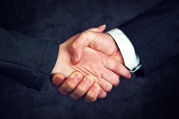 Two businessmen in suits shaking hands