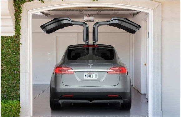 A rendering of a Tesla Model X in a garage, with the falcon-wing doors open
