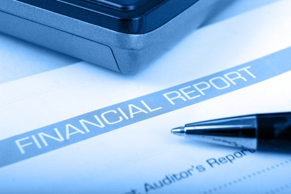 Portion of financial report with tip of pen on top