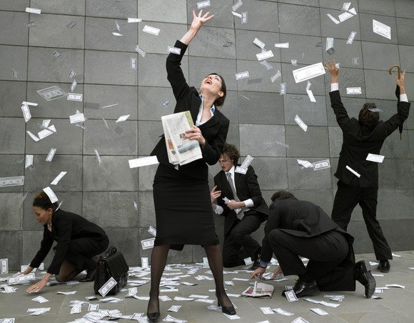 Five people in black business attire collect dollar bills falling from the sky.