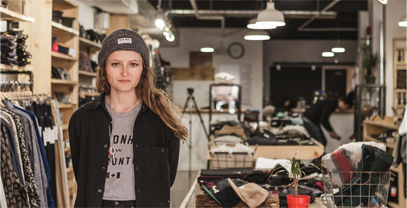 A young woman business owner dressed casually with knit cap in her rustic looking store of clothes that match what she's wearing.
