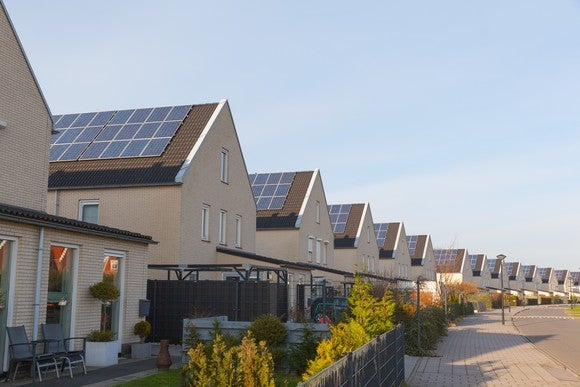 Row of identical homes all with solar panels on their roofs.