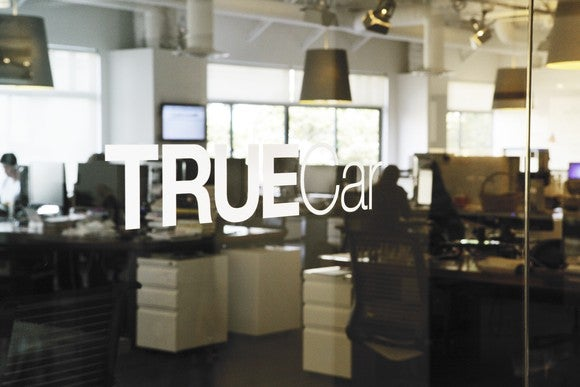 The TrueCar logo on a glass door leading into the company's office space.