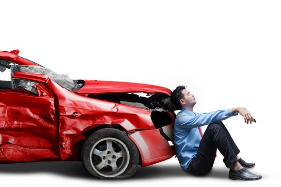 An upset man leaning on the front of a crashed car.