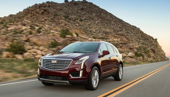 A dark red Cadillac XT5 on a road near a rocky hill.