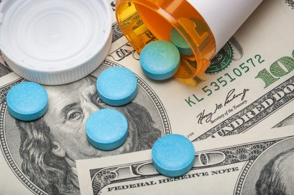 Blue pills spill out of an overturned prescription bottle and onto a pile of hundred-dollar bills.