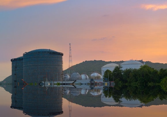 Natural gas liquids storage tanks reflecting on the water.