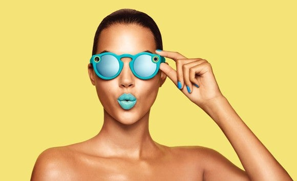 A woman wearing turquoise Snap Spectacles and matching lipstick.