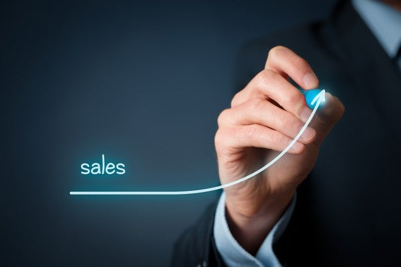 "A businessperson drawing a line labeled ""sales"" that is sloping sharply upwards"