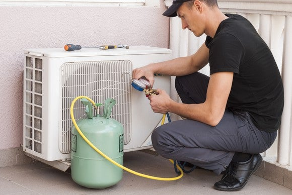 Man adding coolant to an air conditioner.