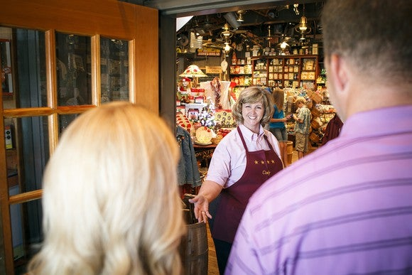 A woman greeting customers into a Cracker Barrel location.