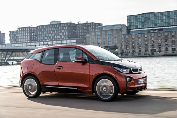 A red BMW i3 sedan on a city waterfront