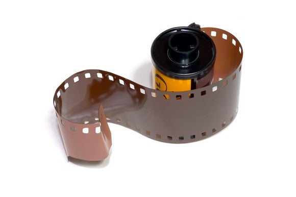 35 mm film roll with a few inches of film pulled out of the container.