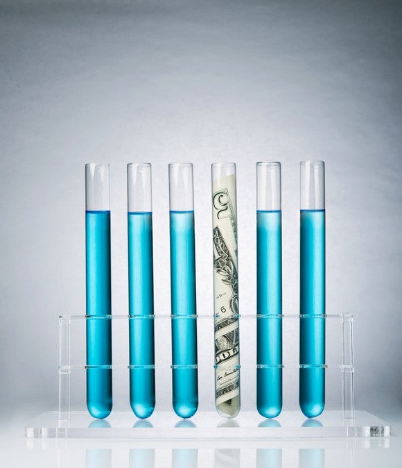 Six test tubes, five with blue liquid and one containing money