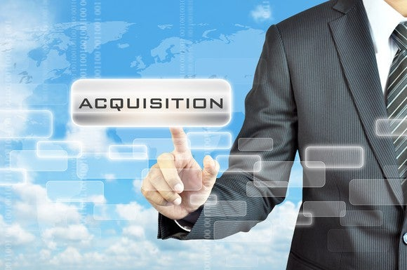 "Man in suit pointing to the word ""acquisition"" shown in foreground"
