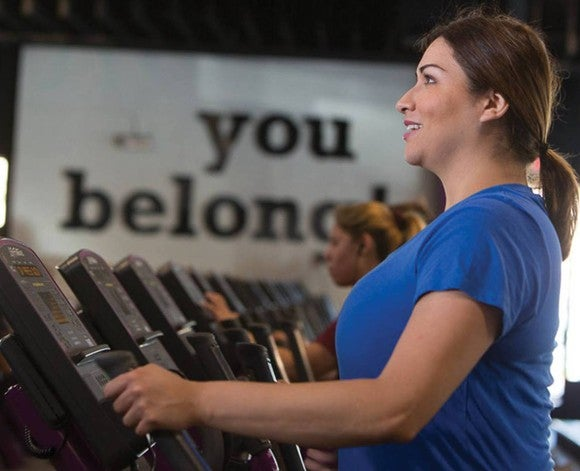 "A woman on an exercise machine with a sign that says ""you belong"" on the wall behind her"