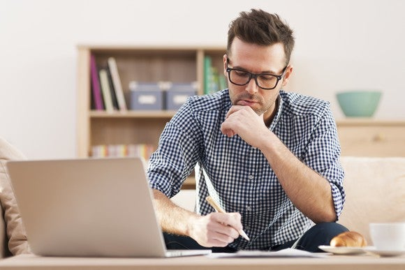 A pensive looking man in front of a laptop.