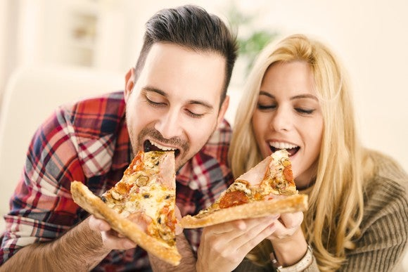 A man and woman each taking a bite out of a slice of pizza.