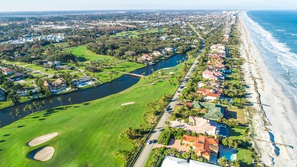 Aerial view of neighborhood between a beach and a golf course