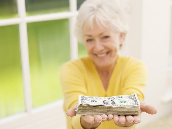 An old woman wearing a yellow shirt holding out a pile of money and smiling.