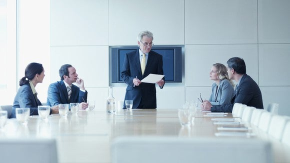 Business people sitting around a table in a conference room.