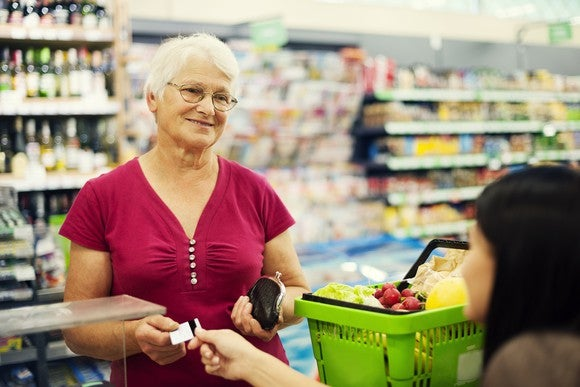 A senior women buying groceries.