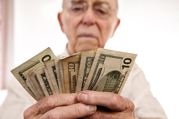 A senior citizen counting his Social Security cash.