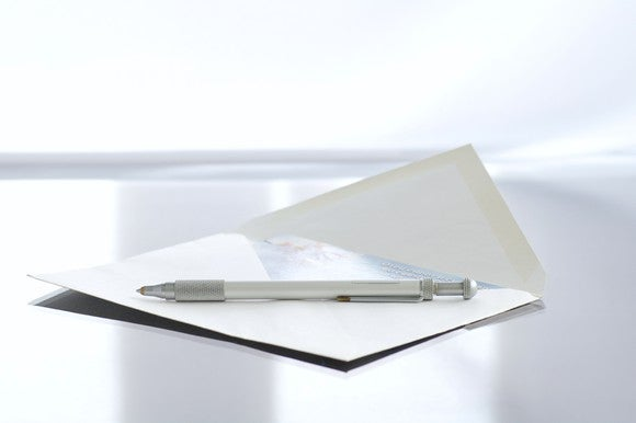 An envelope with a pen sitting on it