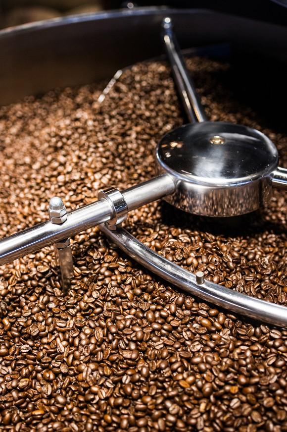 A machine mixes a vat full of coffee beans.