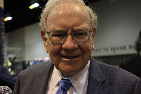 Warren Buffett wearing a gray suit, blue tie, and smiling into the camera
