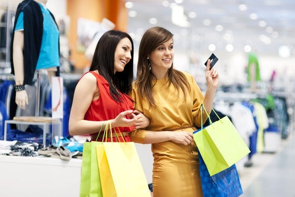 Two women shopping in a department store, one holding a credit card.