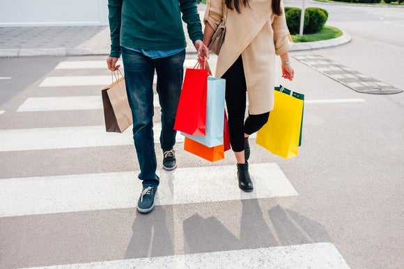 Two people on a crosswalk, holding shopping bags.