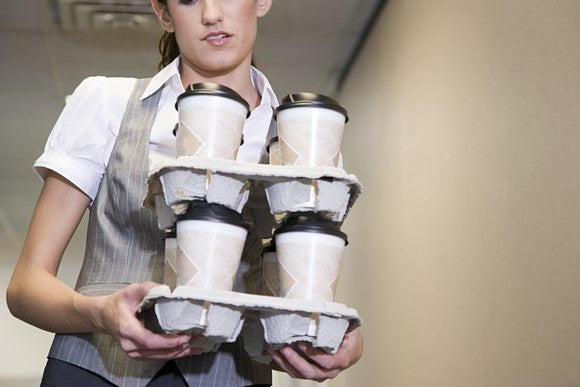 A server balances a stack of to-go coffee cups.