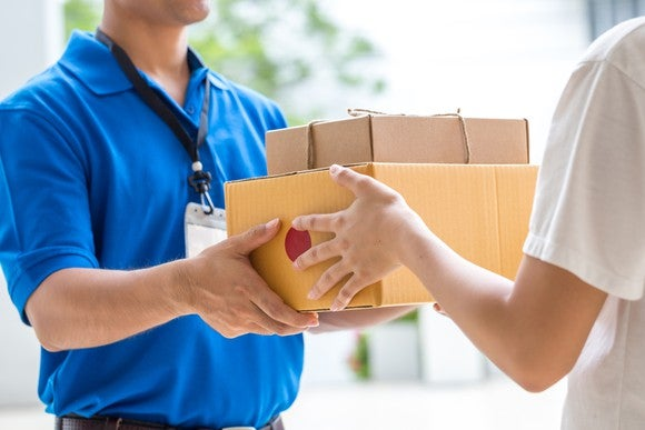 A man hands packages to someone else.