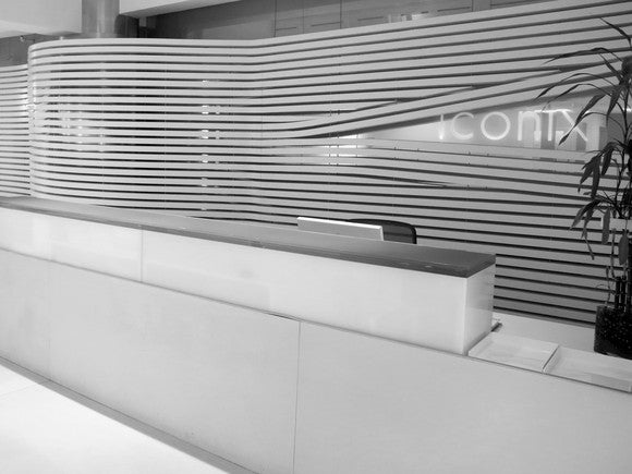 A front desk at Iconix headquarters, in glossy white with the company's logo displayed on the back wall.