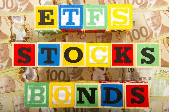 "Wooden blocks arranged to spell ""ETFS"" ""STOCKS"" and ""BONDS"", on a stack of money"
