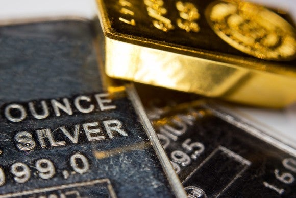 Bars of gold, silver, and palladium resting crosswise on one another, with gold on top.