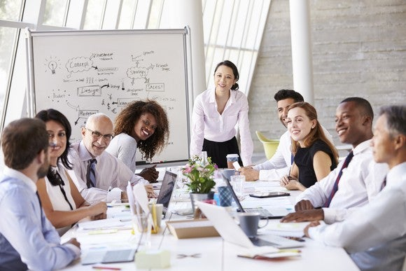 nine people sitting at a conference table at a business meeting, with white board