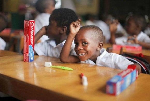 Child in classroom with toothbrush and Colgate toothpaste box.