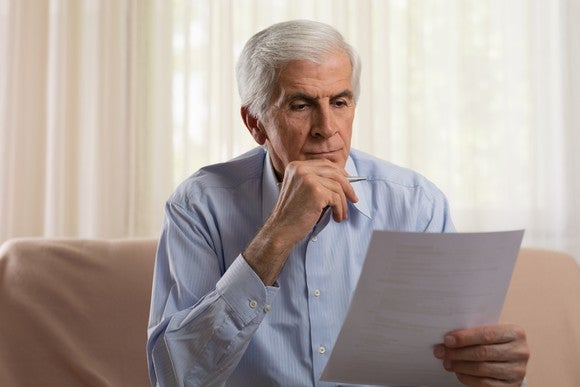 Senior man holding a sheet of paper