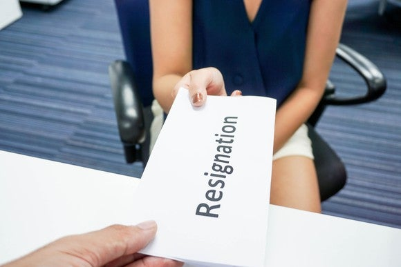 """A woman hands a letter that reads """"Resignation"""" across a table."""