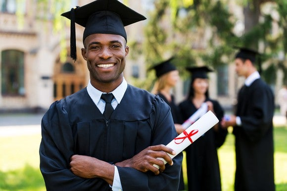 Male in cap and gown holding diploma