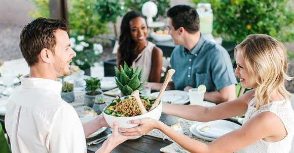 A man passes a bowl of noodles to a woman as a group is sat around a dinner table.
