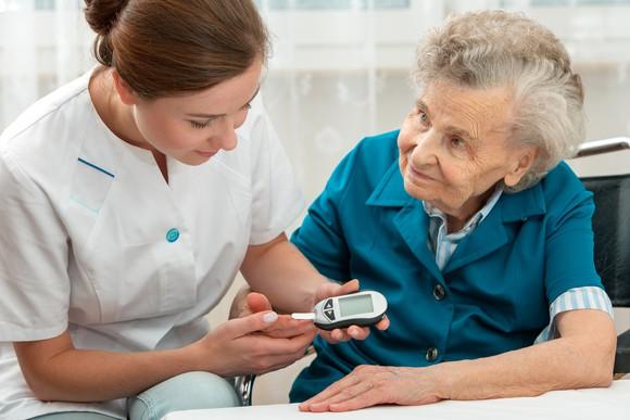 A nurse checks an elderly woman's blood sugar levels using a glucometer.